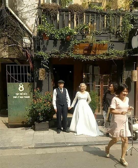 Hình ảnh cô dâu tóc bạc mặc váy cưới trắng, chú rể chống gậy móm mém cười khiến trên phố Hà Nội gây sốt mạng - Ảnh 1.