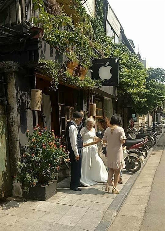 Hình ảnh cô dâu tóc bạc mặc váy cưới trắng, chú rể chống gậy móm mém cười khiến trên phố Hà Nội gây sốt mạng - Ảnh 2.