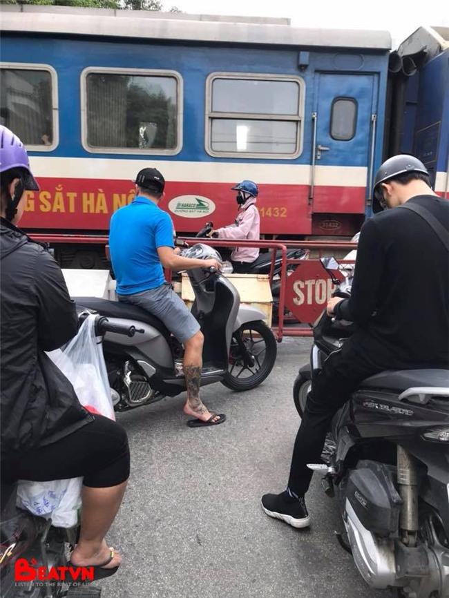 Bức ảnh gây căng thẳng: Cô gái đi xe máy đứng trong khe hẹp giữa đoàn tàu đang chạy và rào chắn - Ảnh 1.
