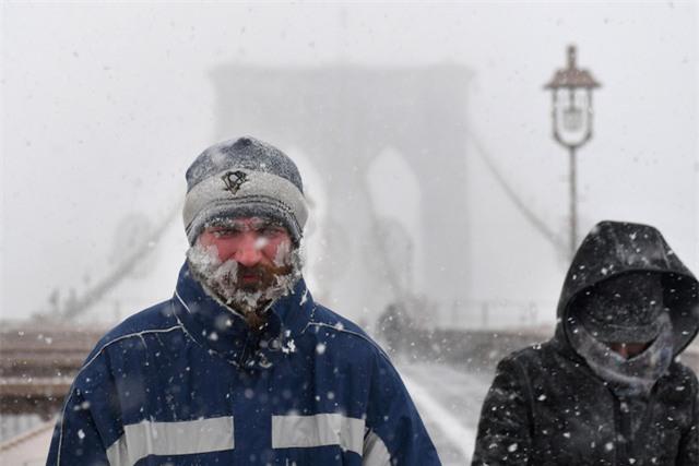 Truyền thông Mỹ đưa tin một người đàn ông 64 tuổi ở bang Ohio đã bị chết cóng ngay trước hiên nhà khi nhiệt độ giảm sâu hôm 3/1. Trong ảnh: Tuyết đóng băng trên gương mặt một người đi bộ tại cây cầu Brooklyn ở thành phố New York. (Ảnh: Reuters)