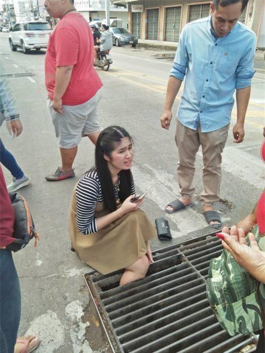 Thái Lan: Mải nghịch điện thoại, cô gái trẻ bất cẩn để lọt chân vào miệng cống ngầm, phải nhờ cứu hộ đến giải thoát - Ảnh 1.