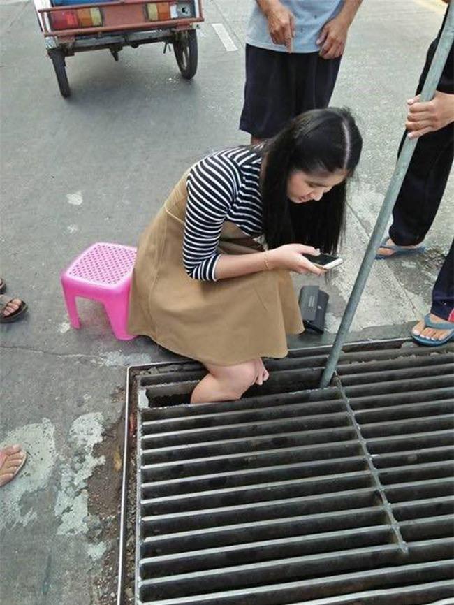 Thái Lan: Mải nghịch điện thoại, cô gái trẻ bất cẩn để lọt chân vào miệng cống ngầm, phải nhờ cứu hộ đến giải thoát - Ảnh 2.