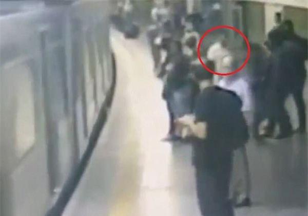 Đang đứng đợi tàu điện, nữ hành khách suýt mất mạng vì một cú đẩy - Ảnh 1.