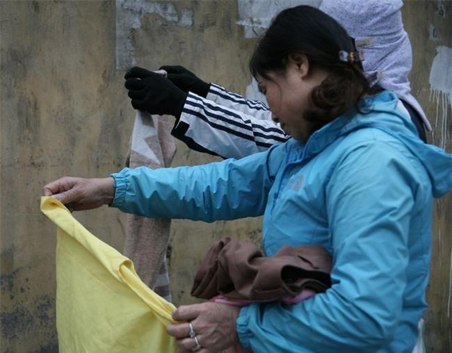 Nhiều người nghèo vui mừng khi kiếm được bộ quần áo miễn phí để diện Tết trên phố Hà Nội - Ảnh 4.