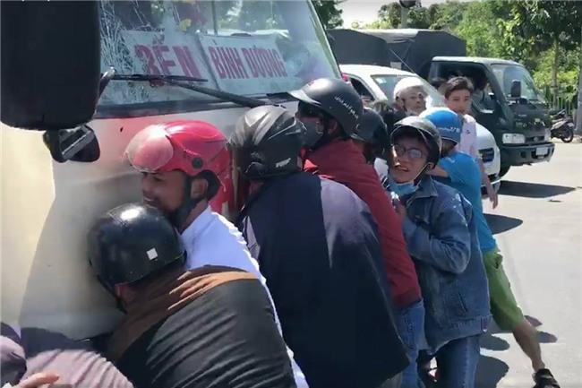 Clip: Ám ảnh ánh mắt của cô gái bị kẹt dưới gầm xe khách trong lúc hàng chục người cố gắng giải cứu