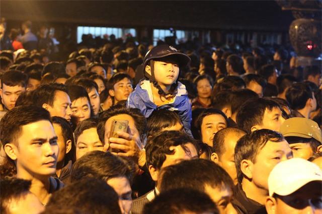 Một đứa trẻ với khuôn mặt mệt mỏi được bố cõng trên vai chờ xếp hàng vào xin ấn cầu lộc cầu tài cho gia đình