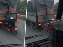 Hình ảnh nam thanh niên đứng trên xe máy, đu bám xe tải đầy nguy hiểm