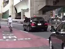 Nhân viên đoàn hộ tống Thủ tướng Nhật Bản cúi đầu chào và cảm ơn người đi xe đạp vì đã nhường đường