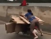 """Tiếc tiền thuê vận chuyển, người phụ nữ Trung Quốc vừa lái xe máy vừa """"làm xiếc"""" giữa đường"""