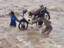Thầy giáo khiêng xe máy băng qua nước lũ đến trường