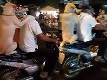 """Chó ngồi xe máy, đặt """"tay"""" lên vai chủ, ngậm ô như làm xiếc trên phố"""