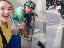 Hai tài xế GrabBike chui xuống cống để nhặt đồ hộ nữ du khách nước ngoài