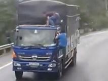 Hai người đàn ông đánh đu trên đầu xe tải