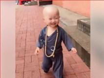 Ngất ngây ngắm nhìn em bé mặc áo tu hành cười khanh khách