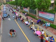 Trung Quốc: Cha mẹ xếp hàng dài 200 mét, dựng lều ngủ qua đêm, chen chúc nhau đăng ký học cho con