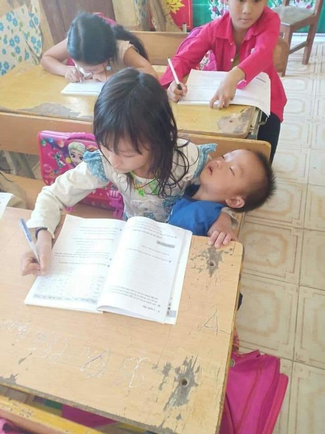 Vừa bế em vừa học bài, tấm hình chụp cô bé tiểu học khiến nhiều người xót xa-1