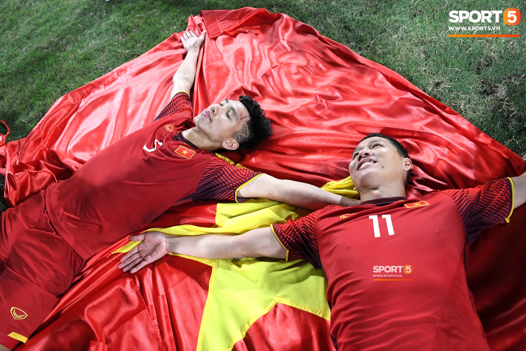 Chú Anh Đức nở nụ cười mãn nguyện, cháu Văn Hậu nhắm mắt mơ màng tạo dáng pose hình với lá cờ trải trên thảm cỏ-1