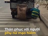 Nhân viên vệ sinh đu vào sau xe đang chạy để nhặt rác ven đường