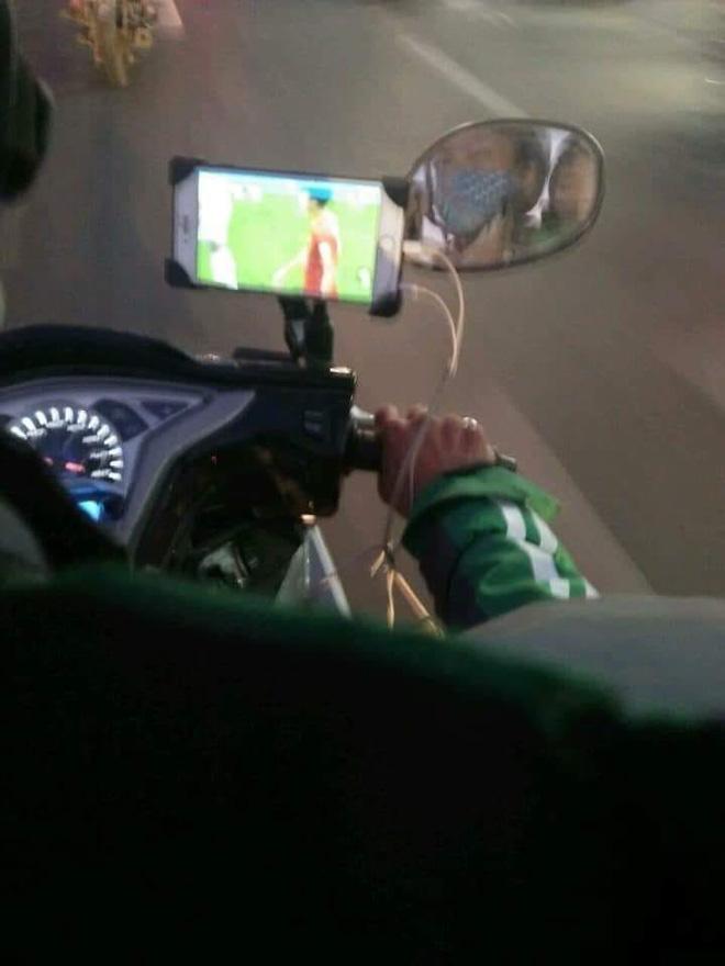 Vừa lái xe vừa dùng điện thoại xem Việt Nam đá, tài xế xe ôm khiến nhiều người lo lắng-1