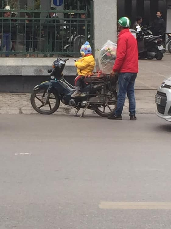 Hình ảnh cháu bé ngồi ngoan trên xe máy giữa cái se lạnh chờ đợi cha đi ship hoa tươi trong ngày 8/3 gây xúc động-2