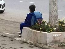 Bé trai ngồi bên đường, bán cà chua