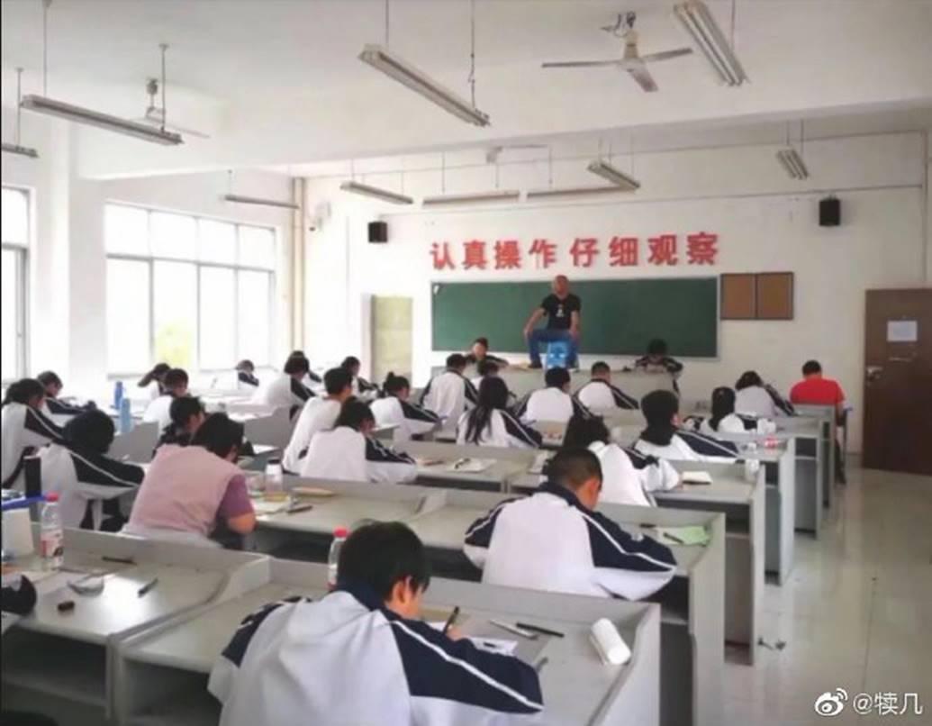 Quá mệt mỏi với những mánh khoé thi cử, thầy giáo bê hẳn ghế lên bàn ngồi coi thi như một vị thần khiến học trò sợ xanh mặt-1