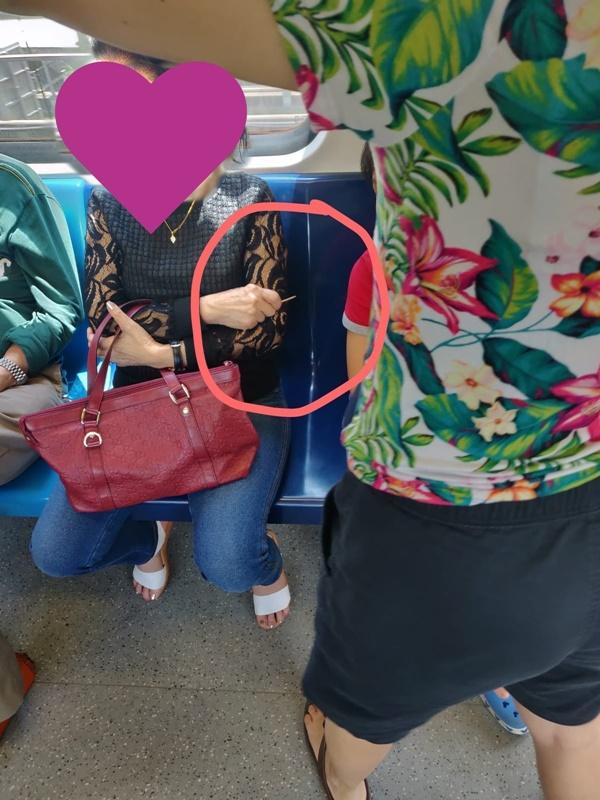 Bức ảnh người phụ nữ cầm cây tăm trên tay, bên cạnh là bé trai đang ngủ gật để tránh đứa trẻ động vào người gây tranh cãi-1