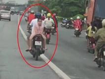 Bố chở con ngồi ngược trên xe máy chạy bon bon trên đường