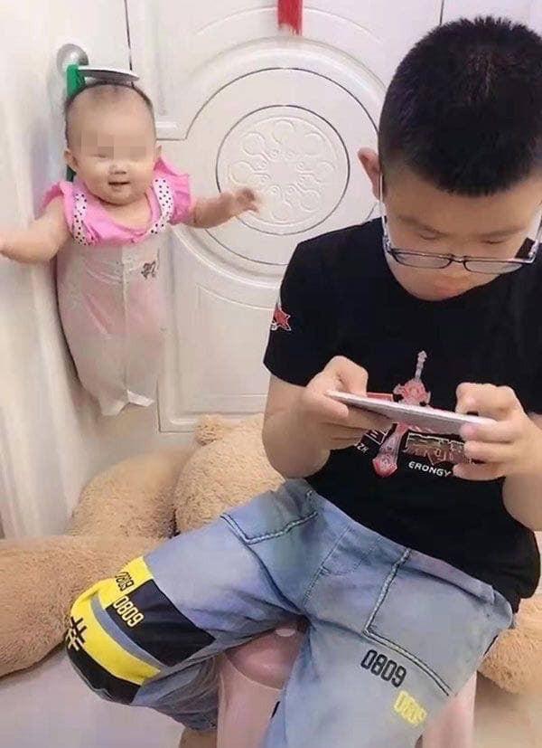 Mẹ nhờ trông em gái, cậu bé có ngay sáng kiến bất ngờ để rảnh tay chơi game-2