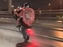 Tài xế mặc áo mưa bốc đầu giữa đường ướt trên cầu