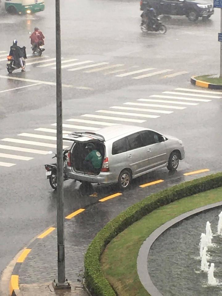 Ô tô 7 chỗ dừng bên góc đường, mở cửa để tài xế xe ôm kịp ngồi trú mưa khiến nhiều người cảm thấy ấm lòng-1