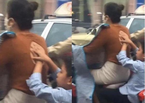 Mẹ chở con trai đi trên đường, hành động của đứa trẻ phía sau gây chú ý và được dân mạng khen ngợi hết lời-1