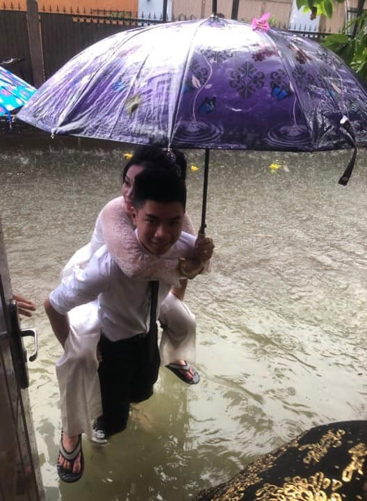 Em gái mưa phiên bản lũ lụt: Câu chuyện đằng sau bức ảnh chú rể cõng cô dâu đứng giữa biển nước đang nổi rần rần MXH-1