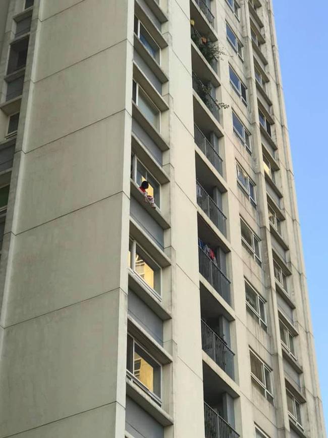 Hình ảnh bé gái ngồi vắt vẻo ngoài ban công tầng 6 chung cư khiến nhiều người kinh hãi-1