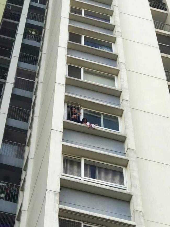 Hình ảnh bé gái ngồi vắt vẻo ngoài ban công tầng 6 chung cư khiến nhiều người kinh hãi-2