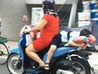 Người phụ nữ buộc đứa trẻ sau xe máy ở TP.HCM