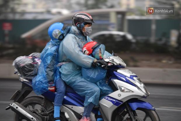Trẻ nhỏ trùm chăn, khoác áo mưa chật vật theo chân bố mẹ rời Thủ đô về quê ăn Tết-1