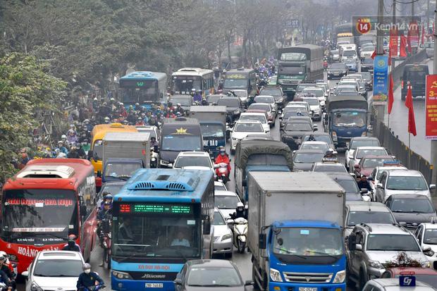 Trẻ nhỏ trùm chăn, khoác áo mưa chật vật theo chân bố mẹ rời Thủ đô về quê ăn Tết-7