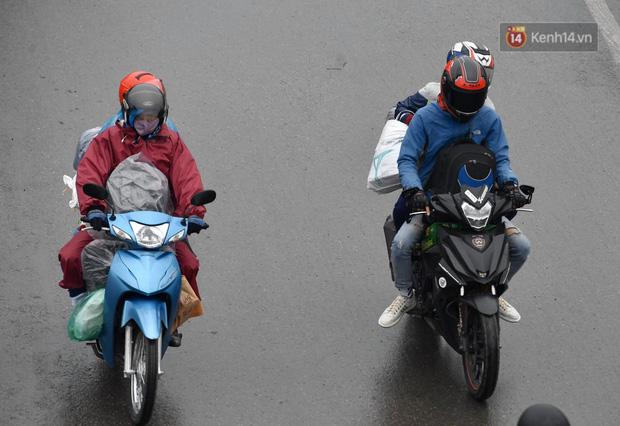 Trẻ nhỏ trùm chăn, khoác áo mưa chật vật theo chân bố mẹ rời Thủ đô về quê ăn Tết-8