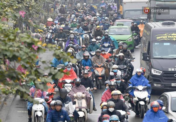 Trẻ nhỏ trùm chăn, khoác áo mưa chật vật theo chân bố mẹ rời Thủ đô về quê ăn Tết-9