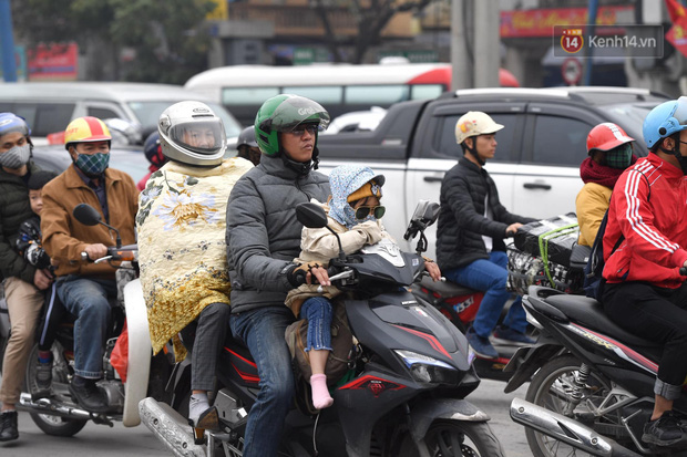 Trẻ nhỏ trùm chăn, khoác áo mưa chật vật theo chân bố mẹ rời Thủ đô về quê ăn Tết-14