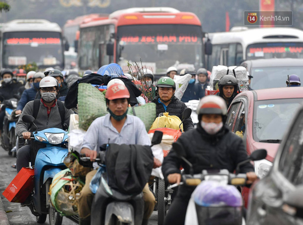 Trẻ nhỏ trùm chăn, khoác áo mưa chật vật theo chân bố mẹ rời Thủ đô về quê ăn Tết-20