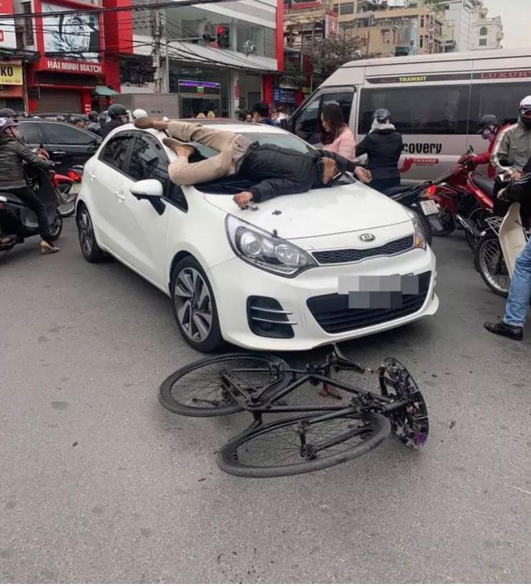 Va chạm giao thông không hòa giải được, chủ xe đạp leo lên nắp capo ô tô nằm-1