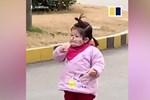 Bé gái cố ăn bánh quy dù đang đeo khẩu trang tránh virus corona
