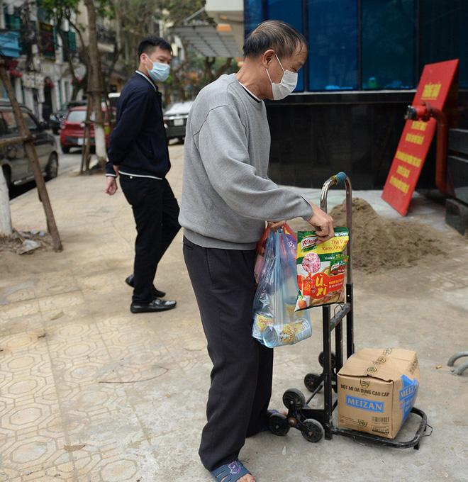 Người dân sống trong khu cách ly trên phố Trúc Bạch mang xe đẩy nhận nhu yếu phẩm-6