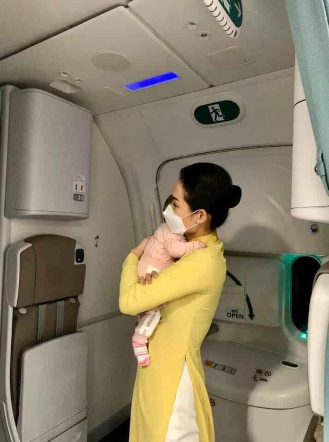 Hình ảnh nữ tiếp viên hàng không tận tình bế ẵm em bé mới 2 tháng tuổi đã phải xa mẹ về Việt Nam được nhiều người nổi tiếng chia sẻ đầy xúc động-1