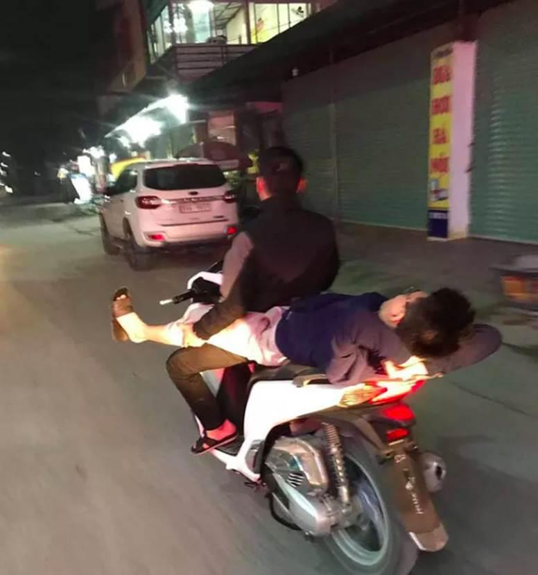 Nam thanh niên nằm duỗi chân, gác vào đùi người lái xe máy đang phóng với tốc độ cao khiến nhiều người sợ hãi-1