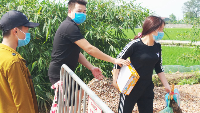 Sau khi công bố bệnh nhân 266 nhiễm COVID-19 ở Hà Nội, phong tỏa các cửa ngõ toàn xã Dũng Tiến, người dân nhờ tiếp thực phẩm qua hàng rào-4
