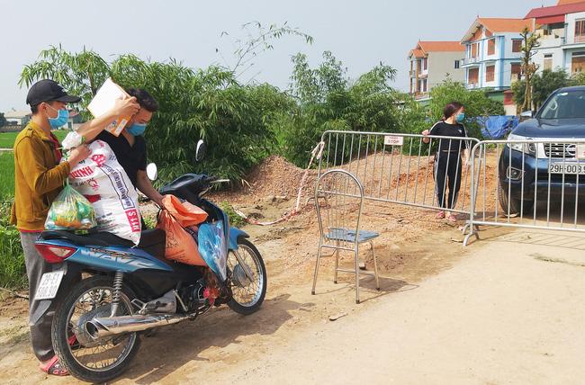 Sau khi công bố bệnh nhân 266 nhiễm COVID-19 ở Hà Nội, phong tỏa các cửa ngõ toàn xã Dũng Tiến, người dân nhờ tiếp thực phẩm qua hàng rào-5