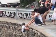 Rùng mình khoảnh khắc người đàn ông nắm tay đứa trẻ đang lơ lửng bên mép đường, bức xúc hơn cả là việc làm của người còn lại